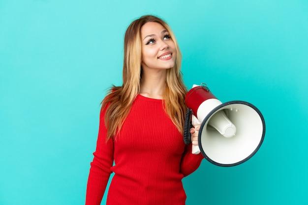 Nastoletnia blondynka na odosobnionym niebieskim tle trzymająca megafon i patrząca w górę podczas uśmiechania się