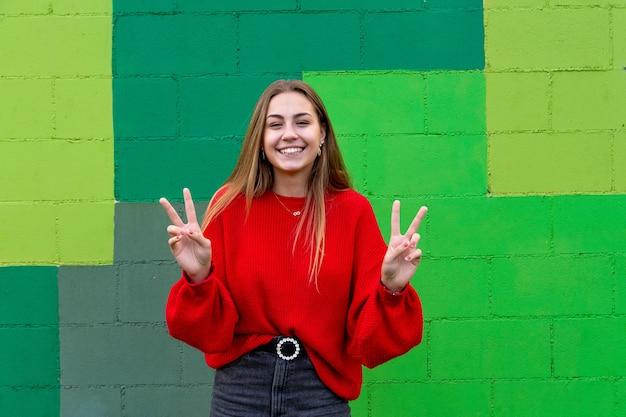 Nastoletnia blondynka robi gesty szczęścia i pozytywności.