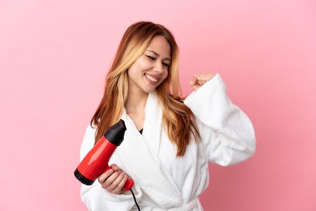 Nastoletnia blondynka świętująca zwycięstwo trzymająca suszarkę do włosów na różowym tle