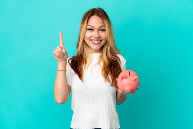 Nastoletnia blondynka trzyma skarbonkę nad odosobnionym niebieskim tłem, wskazując na świetny pomysł