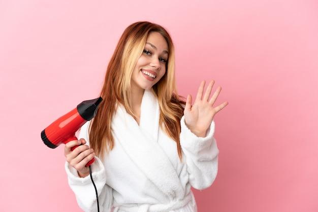 Nastoletnia blondynka trzyma suszarkę do włosów na białym tle, pozdrawiając ręką ze szczęśliwym wyrazem twarzy
