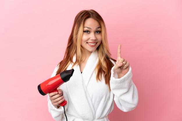 Nastoletnia blondynka trzyma suszarkę do włosów na białym tle, wskazując na świetny pomysł