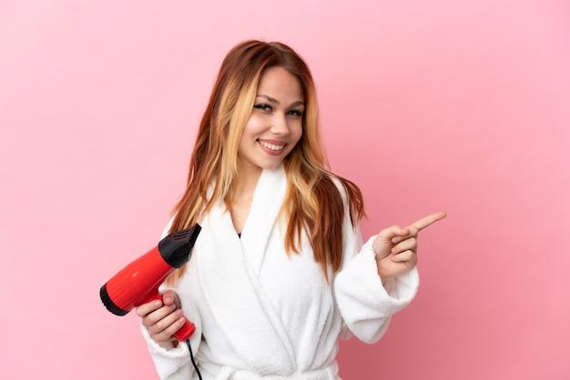 Nastoletnia blondynka trzyma suszarkę do włosów na białym tle, wskazując palcem w bok