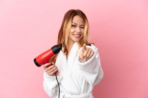 Nastoletnia blondynka trzyma suszarkę do włosów na białym tle, wskazując przód ze szczęśliwym wyrazem twarzy