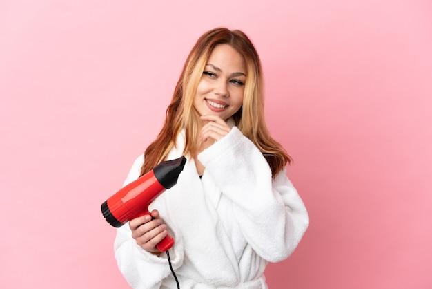 Nastoletnia blondynka trzyma suszarkę do włosów na różowym tle, patrząc w bok i uśmiechając się