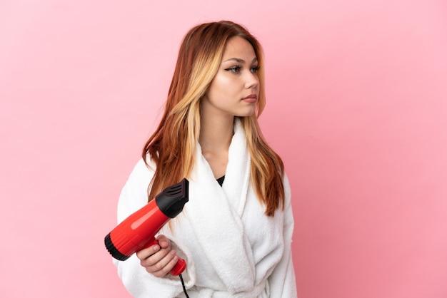 Nastoletnia blondynka trzyma suszarkę do włosów na różowym tle, patrząc w bok