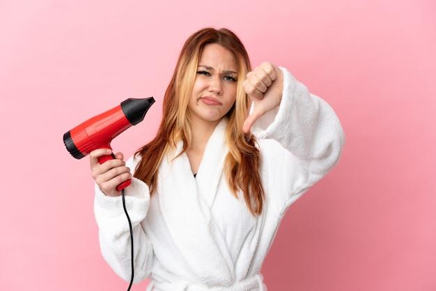 Nastoletnia blondynka trzyma suszarkę do włosów na różowym tle pokazując kciuk w dół z negatywnym wyrazem twarzy