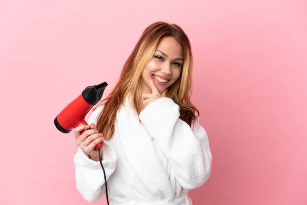Nastoletnia blondynka trzyma suszarkę do włosów na różowym tle szczęśliwa i uśmiechnięta