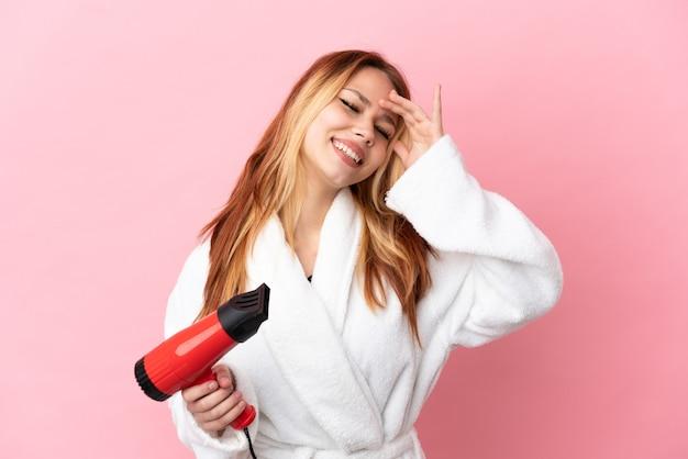 Nastoletnia blondynka trzyma suszarkę do włosów na różowym tle, uśmiechając się dużo
