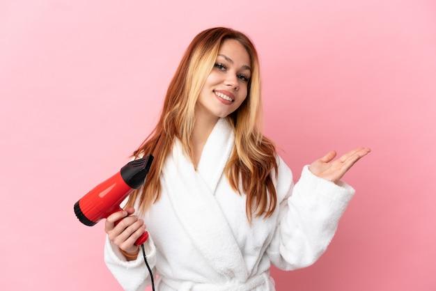 Nastoletnia blondynka trzyma suszarkę do włosów na różowym tle, wyciągając ręce do boku, zapraszając do przyjścia