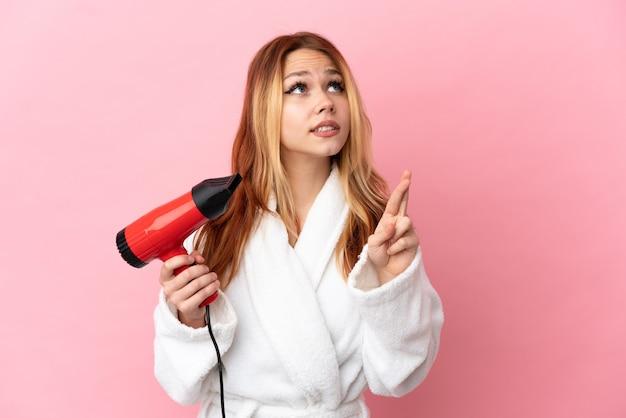 Nastoletnia blondynka trzyma suszarkę do włosów na różowym tle z palcami krzyżującymi i życzącymi wszystkiego najlepszego
