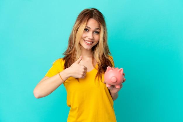 Nastoletnia blondynka trzymająca skarbonkę na odosobnionym niebieskim tle, pokazująca gest kciuka w górę