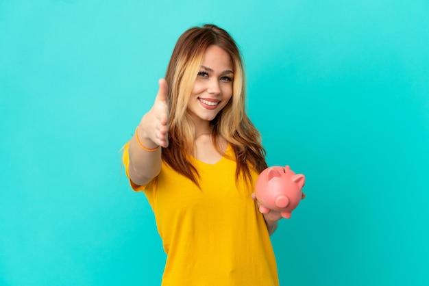 Nastoletnia blondynka trzymająca skarbonkę nad odosobnionym niebieskim tłem, ściskając ręce, aby zamknąć dobrą ofertę