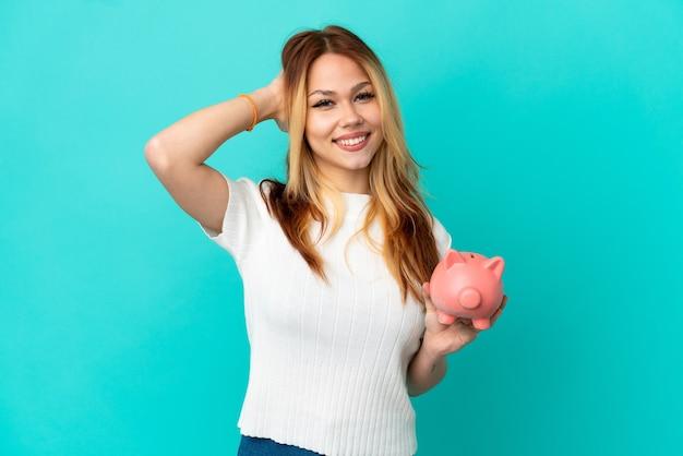 Nastoletnia blondynka trzymająca skarbonkę nad odosobnionym niebieskim tłem śmiejąca się