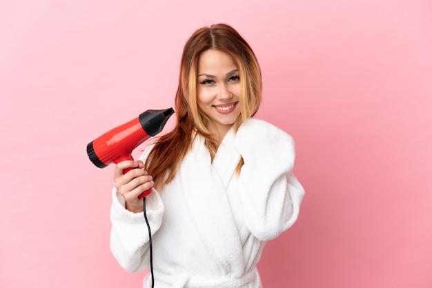 Nastoletnia blondynka trzymająca suszarkę do włosów na białym tle, śmiejąca się