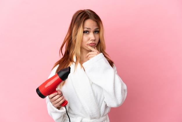 Nastoletnia blondynka trzymająca suszarkę do włosów na odosobnionym różowym tle myślenia