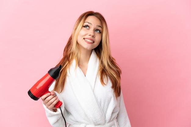 Nastoletnia blondynka trzymająca suszarkę do włosów na różowym tle, myśląca o pomyśle, patrząc w górę