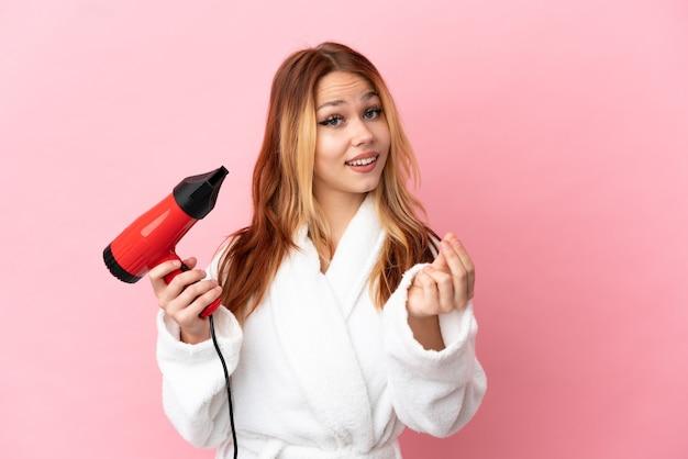 Nastoletnia blondynka trzymająca suszarkę do włosów na różowym tle robienia pieniędzy gest