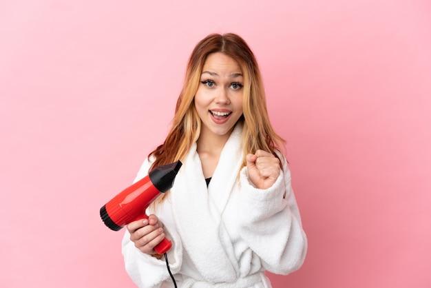 Nastoletnia blondynka trzymająca suszarkę do włosów na różowym tle świętująca zwycięstwo w pozycji zwycięzcy