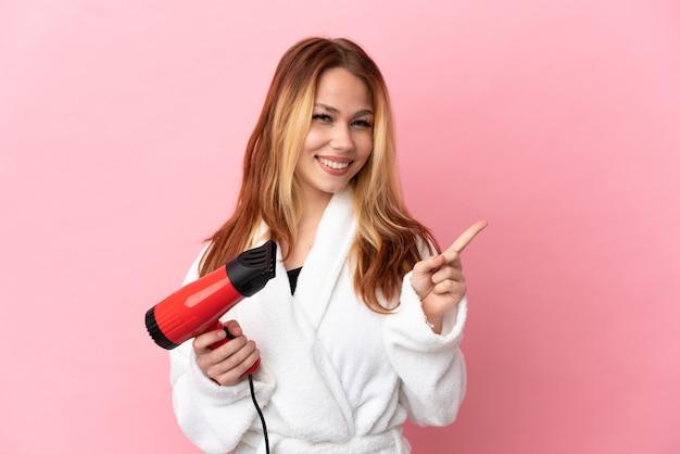 Nastoletnia blondynka trzymająca suszarkę na białym tle, wskazująca na bok, aby zaprezentować produkt