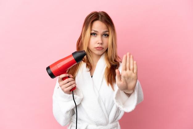 Nastoletnia blondynka trzymająca suszarkę na białym tle, wykonująca gest zatrzymania