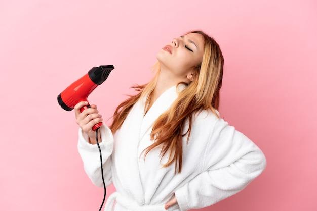 Nastoletnia blondynka trzymająca suszarkę na różowym tle, cierpiąca na ból pleców za wysiłek