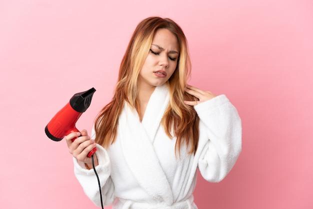 Nastoletnia blondynka trzymająca suszarkę na różowym tle, cierpiąca na ból w ramieniu za wysiłek