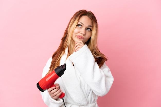 Nastoletnia blondynka trzymająca suszarkę na różowym tle i patrząca w górę