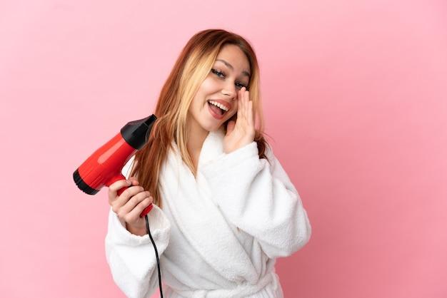 Nastoletnia blondynka trzymająca suszarkę na różowym tle krzycząca z szeroko otwartymi ustami