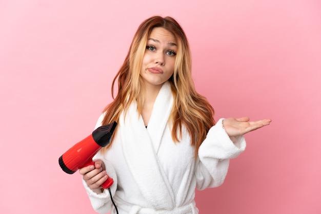 Nastoletnia blondynka trzymająca suszarkę na różowym tle, mająca wątpliwości podczas podnoszenia rąk
