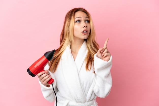 Nastoletnia blondynka trzymająca suszarkę na różowym tle, myśląca o pomyśle wskazującym palcem w górę