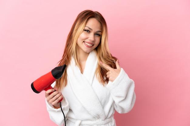 Nastoletnia blondynka trzymająca suszarkę na różowym tle, pokazująca gest kciuka w górę