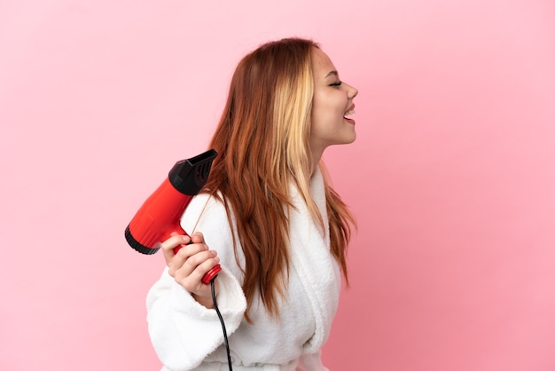 Nastoletnia blondynka trzymająca suszarkę na różowym tle, śmiejąca się w pozycji bocznej