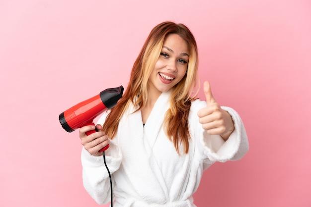 Nastoletnia blondynka trzymająca suszarkę na różowym tle z kciukami do góry, ponieważ stało się coś dobrego