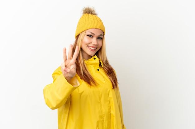 Nastoletnia blondynka ubrana w płaszcz przeciwdeszczowy na białym tle szczęśliwa i licząca trzy palcami