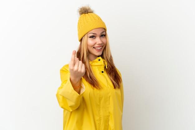 Nastoletnia blondynka ubrana w przeciwdeszczowy płaszcz nad odosobnioną białą powierzchnią robi gest nadchodzący