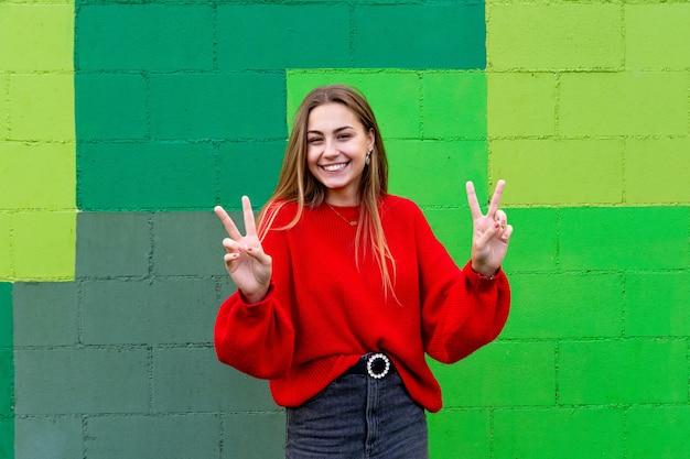 Nastoletnia blondynka w czerwonym swetrze. postawa i gesty szczęścia i pozytywności.