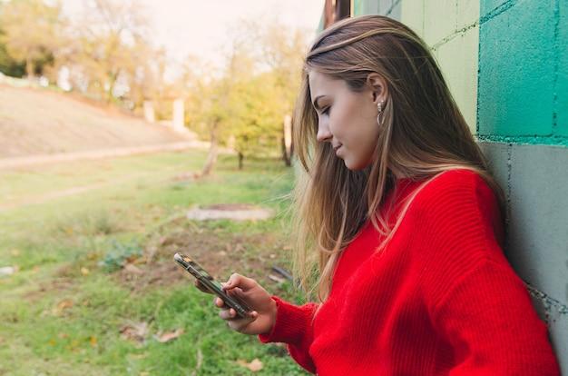 Nastoletnia blondynka w czerwonym swetrze przy użyciu swojego telefonu.