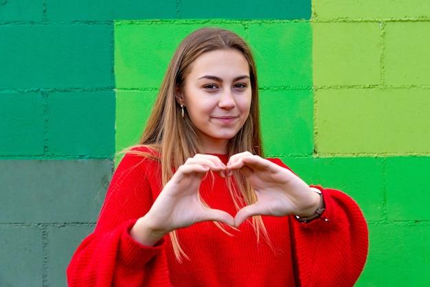 Nastoletnia blondynka w czerwonym swetrze. robi gest serca palcami.