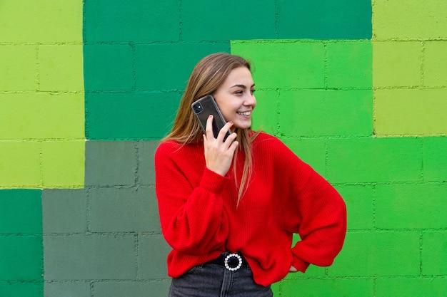 Nastoletnia blondynka w czerwonym swetrze rozmawia ze swoim telefonem komórkowym.