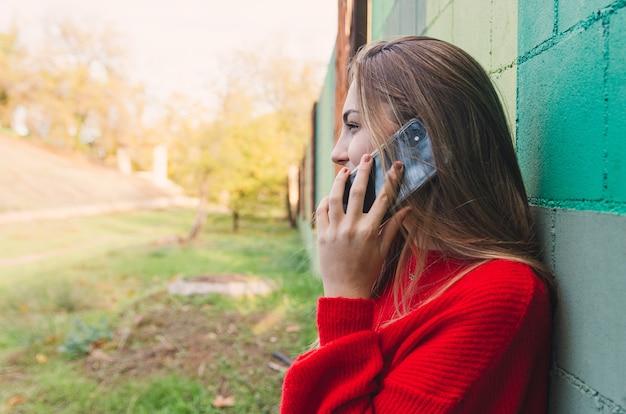 Nastoletnia blondynka w czerwonym swetrze rozmawia ze swoim telefonem.
