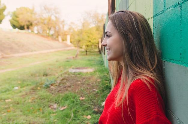 Nastoletnia blondynka w czerwonym swetrze. uśmiechnięty.