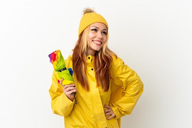 Nastoletnia blondynka w płaszczu przeciwdeszczowym na białym tle, pozuje z rękami na biodrach i uśmiecha się