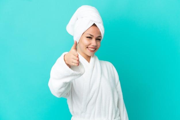 Nastoletnia blondynka w szlafroku na odosobnionym niebieskim tle, ściskając ręce, aby zamknąć dobrą ofertę