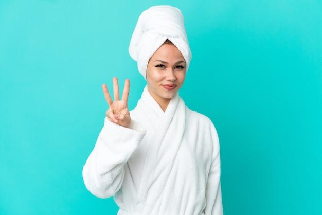 Nastoletnia blondynka w szlafroku na odosobnionym niebieskim tle szczęśliwa i licząca trzy palcami