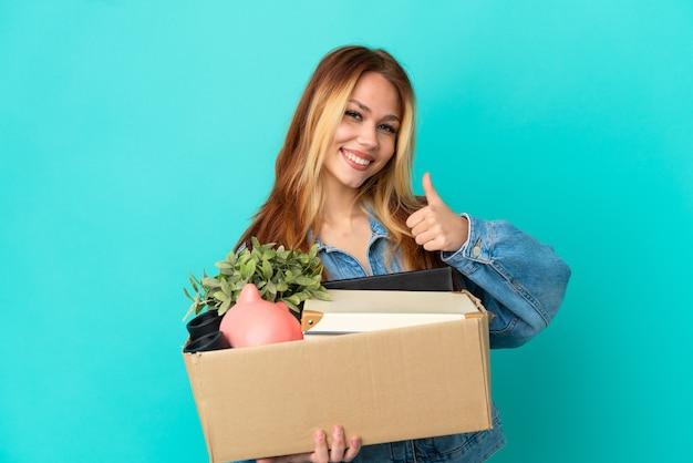 Nastoletnia blondynka wykonująca ruch, podnosząca pudełko pełne rzeczy, pokazująca gest kciuka w górę