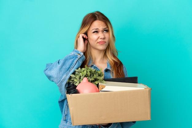 Nastoletnia blondynka wykonuje ruch podczas podnoszenia pudełka pełnego rzeczy sfrustrowanych i zakrywających uszy