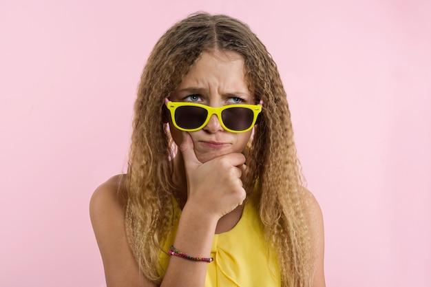 Nastoletnia blondynka z kręconymi włosami marszczy brwi