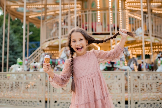 Nastoletnia brunetka dziewczyna trzyma warkocz i zjada lody w parku