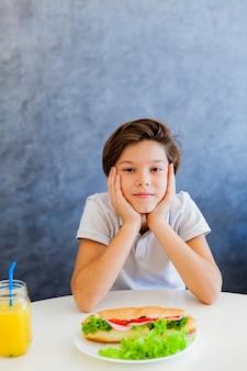 Nastoletnia chłopiec ma śniadanie w domu
